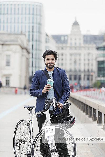 Porträt eines lächelnden Geschäftsmannes mit Kaffee und Fahrrad auf der Stadtbrücke