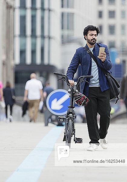 Geschäftsmann mit Smartphone geht Fahrrad auf Stadtbrücke
