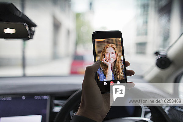 POV Video-Chat der Frau auf dem Bildschirm eines Smartphones im Auto