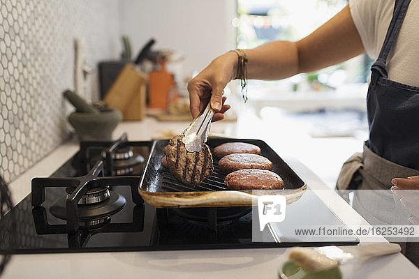Frau beim Grillen von Hamburgern am Küchenherd