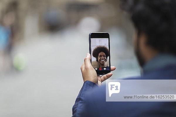 Mann im Video-Chat mit Frau auf dem Bildschirm eines Smartphones