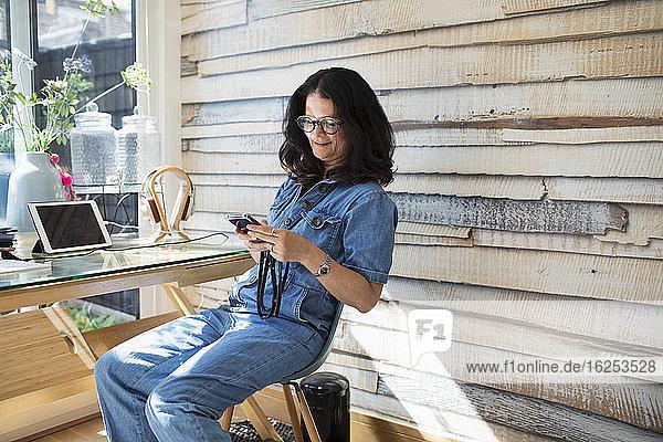 Lächelnde Frau benutzt Smartphone im Home-Office