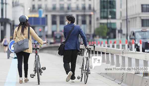 Geschäftsleute mit Gesichtsmasken beim Radfahren auf der Stadtbrücke
