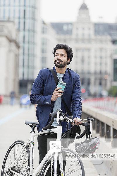 Lächelnder Geschäftsmann mit Kaffee und Fahrrad auf der Stadtbrücke