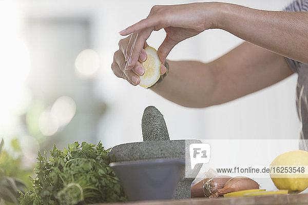 Frau gibt Zitronensaft in Mörser und Stößel in der Küche