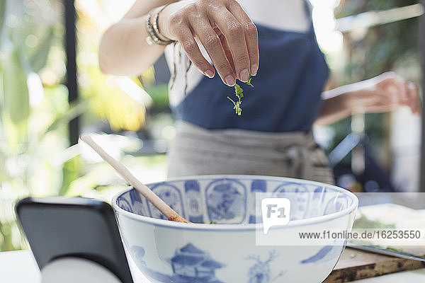 Woman sprinkling fresh herbs in bowl