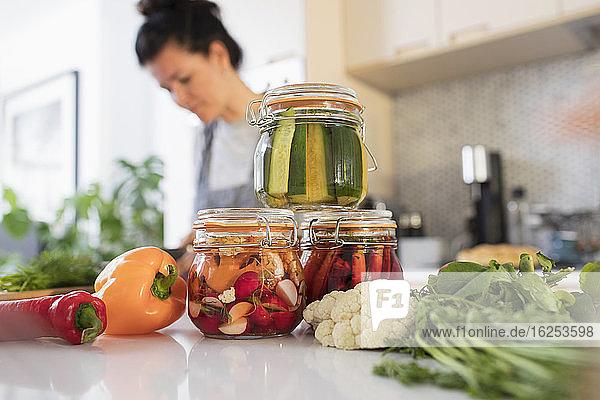 Frau konserviert Gemüse in Gläsern an der Küchentheke