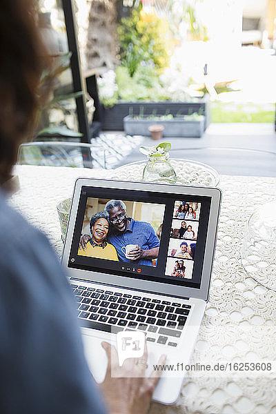 Frau im Video-Chat mit Familie und Freunden am Laptop-Bildschirm