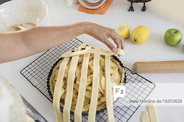 Frau arrangiert Gitter über Apfelkuchen in der Küche