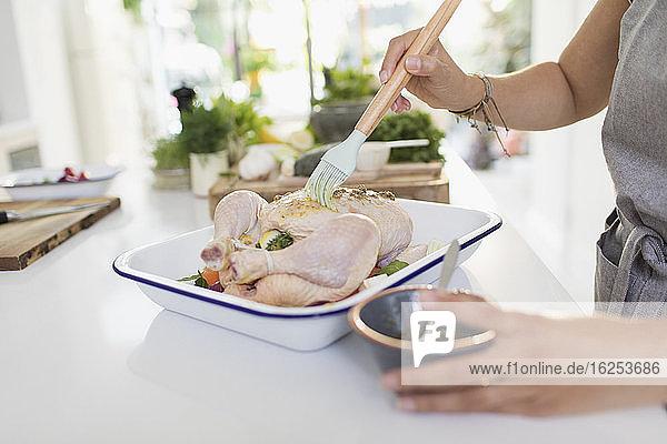 Frau  die in der Küche rohes Hühnerfleisch mit Soße bürstet