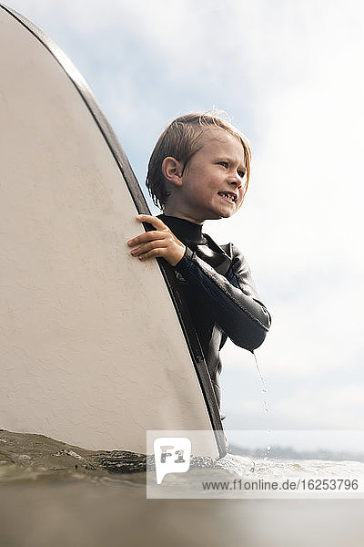 Portrait of young boy wearing wet suit,  carrying surfboard into ocean,  Santa Barbara,  California,  USA.