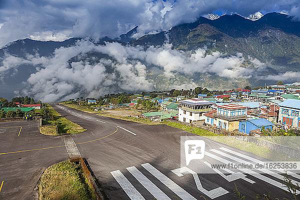 Der berühmte Flughafen in Lukla  Nepal  gilt als eine der gefährlichsten Start- und Landebahnen der Welt mit einer Neigung von 11 Grad und steilen Himalyan-Bergen an beiden Enden  mit dem Dorf hinter der Start- und Landebahn  an einer Wetterpause an einem sonnigen und bewölkten Herbsttag; Lukla  Bezirk Solukhumbu  Nepal