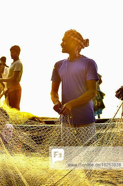 Fischer beim Reinigen eines Fischernetzes am Strand von Puri; Puri  Bundesstaat Odisha  Indien