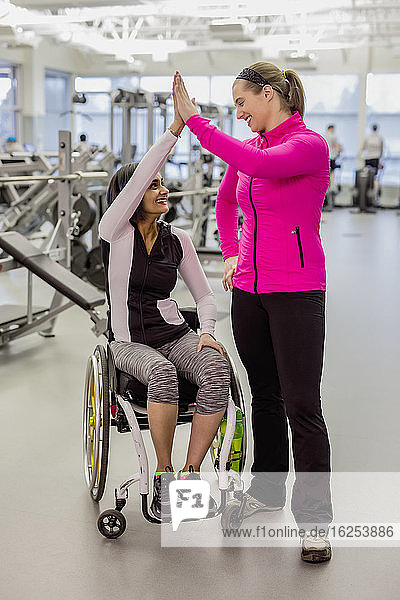 A paraplegic woman and her trainer give a high five after a successful workout in a recreational facility: Sherwood Park  Alberta  Canada