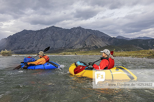 Ein kaukasischer Mann im orangefarbenen Trockenanzug paddelt mit seinem blauen Ruderboot den Fluss hinunter  während eine kaukasische Frau im roten Trockenanzug mit ihrem gelben Boot hinter ihm den Marsh Fork River hinunter paddelt. Sie sind an einem sonnigen Sommertag im Arctic National Wildlife Refuge von den Brooks Range-Bergen umgeben; Alaska  Vereinigte Staaten von Amerika