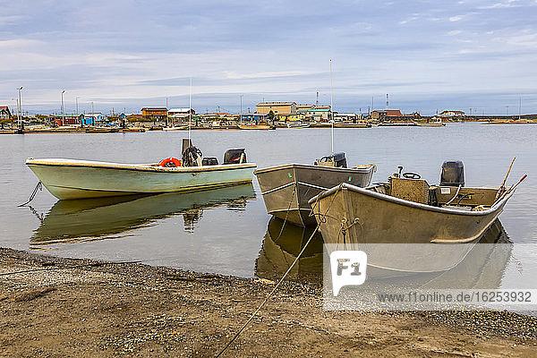 Fischerboote ankerten an einem Spätsommerabend im Schwanensee mit einigen Gebäuden in der Stadt und Booten auf der anderen Seite des Sees; Kotzebue  Alaska  Vereinigte Staaten von Amerika