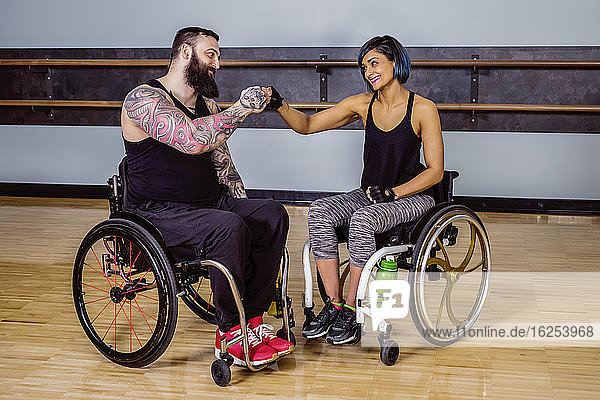 Two paraplegic friends giving each other a fist bump of encouragement after working out at a fitness facility: Sherwood Park  Alberta  Canada