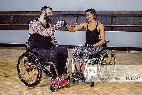 Zwei querschnittsgelähmte Freunde  die sich nach dem Training in einer Fitnesseinrichtung gegenseitig einen Faustschlag der Ermutigung geben: Sherwood Park  Alberta  Kanada