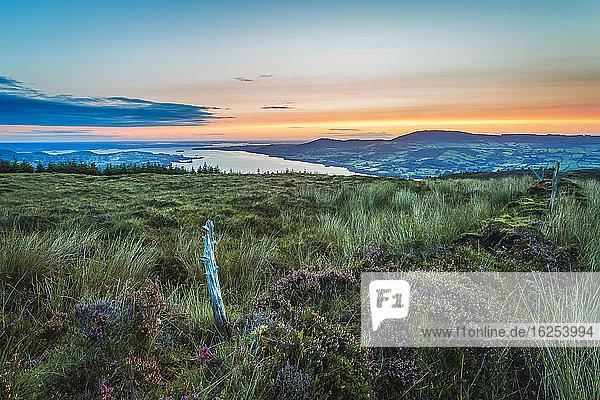 Ein alter Holzzaunpfahl auf einem Moorhügel mit Blick auf den See Lough Derg in der Ferne bei Sonnenaufgang; Grafschaft Clare  Irland