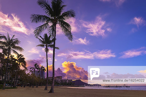 Sunrise over Waikiki with glowing clouds and an empty beach; Waikiki  Oahu  Hawaii  United States of America