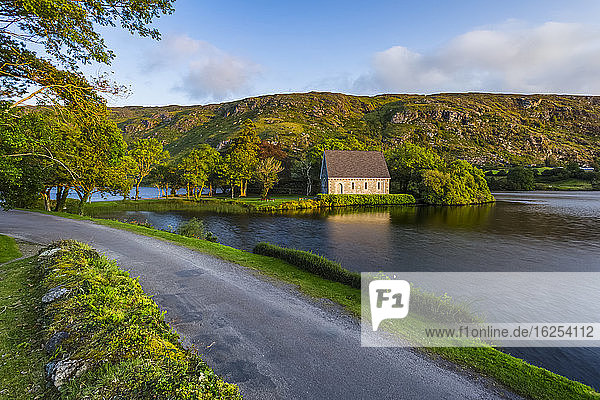 A small road leading down the lake to Gougane Barra with hills in the background in late summer; Gougane Barra  County Cork  Ireland