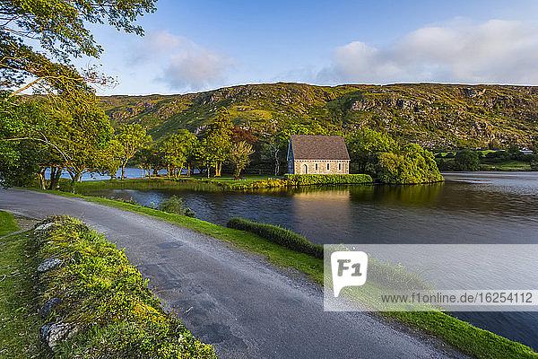 Eine kleine Straße  die den See hinunter nach Gougane Barra führt  mit Hügeln im Hintergrund im Spätsommer; Gougane Barra  Grafschaft Cork  Irland