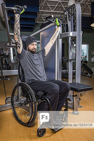 A paraplegic man working out using an overhead press in fitness facility; Sherwood Park  Alberta  Canada