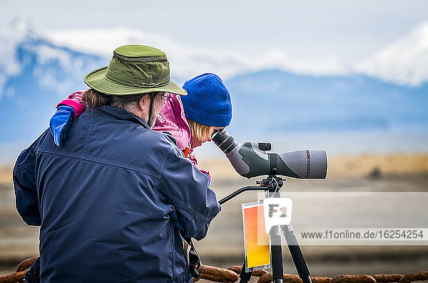 A man holds his daughter to look through a spotting scope during the 21st annual 2013 Kachemak Bay Shorebird Festival. The festival is held in Homer  Alaska  sponsored by the Homer Chamber of Commerce and US Fish & Wildlife Service; Homer  Alaska  United States of America