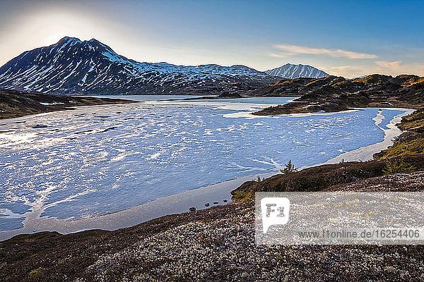 Halb gefrorener Verlorener See bei Sonnenuntergang  im Hintergrund die Chugach-Berge. Chugach National Forest  Kenai-Halbinsel  Süd-Zentral-Alaska im Frühling; Seward  Alaska  Vereinigte Staaten von Amerika