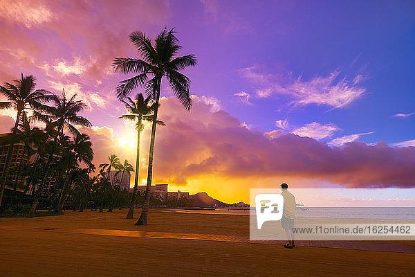 Ein Mann steht am Strand von Waikiki und blickt bei Sonnenaufgang auf die Eigentumswohnungen und Palmen entlang der Küstenlinie von Waikiki; Honolulu  Oahu  Hawaii  Vereinigte Staaten von Amerika