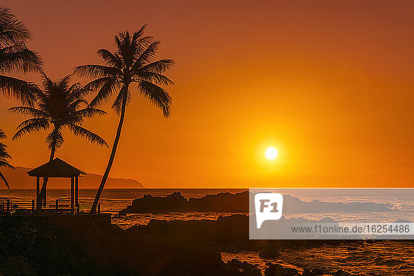 Sunset glowing in an orange sky with silhouetted rock  gazebo and palm trees along the waterfront; Oahu  Hawaii  United States of America