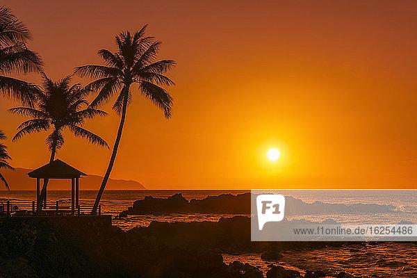 Sonnenuntergang am orangefarbenen Himmel mit silhouettiertem Felsen  Pavillon und Palmen entlang der Uferpromenade; Oahu  Hawaii  Vereinigte Staaten von Amerika