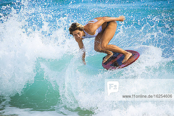 Eine junge Frau  die auf einer Welle vor Sandy Beach  Oahu; Oahu  Hawaii  Vereinigte Staaten von Amerika  auf dem Skimboard fährt