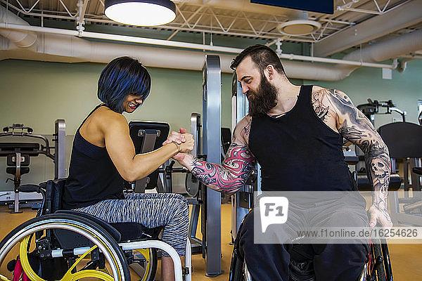 Zwei querschnittsgelähmte Freunde  die nach dem Training in einer Fitnesseinrichtung vorgeben  Armdrücken zu machen: Sherwood Park  Alberta  Kanada