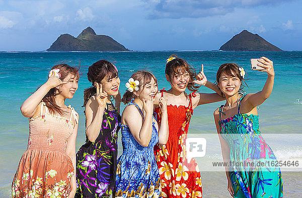 Eine Gruppe japanischer Studenten im Urlaub am Strand von Lanakai mit den Mokes-Inseln im Hintergrund: Oahu  Hawaii  Vereinigte Staaten von Amerika
