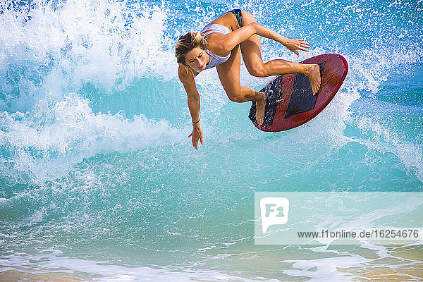 A young woman leaps in the air on a skimboard off Sandy Beach  Oahu; Oahu  Hawaii  United States of America