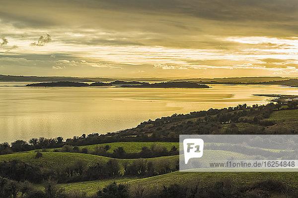 Grüne Felder und Landschaft mit Blick auf die Inseln an der Shannon-Mündung an einem bewölkten Tag bei Sonnenuntergang; Coney Island  Grafschaft Clare  Irland