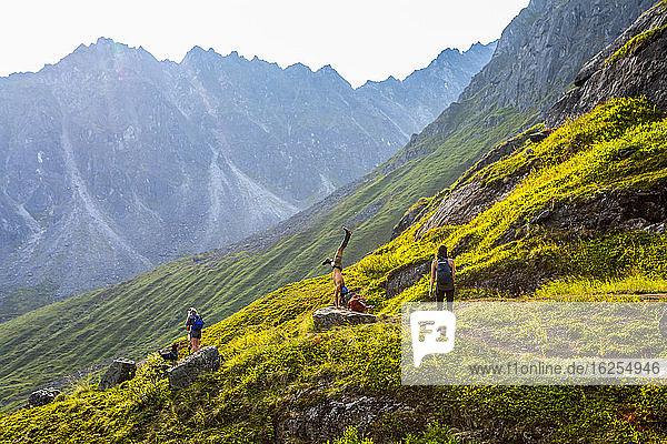 Zwei kaukasische Frauen wandern mit ihrem Hund  wobei ein asiatischer Mann einen Handstand auf einem Felsblock zwischen den beiden Frauen auf dem sehr felsigen/felsenreichen Reed Lakes-Pfad durch die Talkeetna-Berge am Hatcher's Pass  Palmer  Alaska  am späten Nachmittag im Sommer macht; Palmer  Alaska  Vereinigte Staaten von Amerika