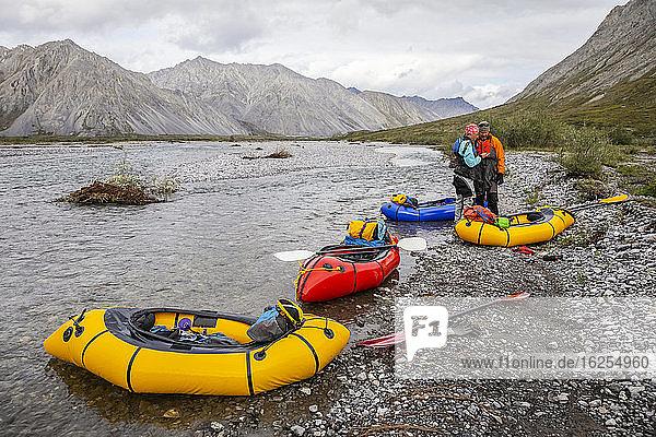 Ein kaukasischer Mann und eine kaukasische Frau schauen mit ihrem Handy am Rande des Marsh Fork-Flusses über Karten  mit vier Ruderflößen (gelb  rot und blau)  die darauf ausgerichtet sind  an einem bewölkten Tag in der Brooks Range  dem arktischen nationalen Wildschutzgebiet  flussabwärts zu treiben; Alaska  Vereinigte Staaten von Amerika