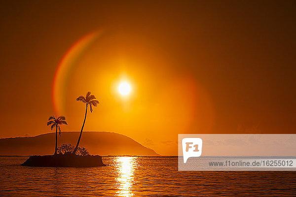 Sonnenaufgang am Kahala Beach  Wai?alae Beach Park  mit einer Fackel um die Sonne in einem leuchtend roten Himmel  der sich im ruhigen Wasser spiegelt; Oahu  Hawaii  Vereinigte Staaten von Amerika