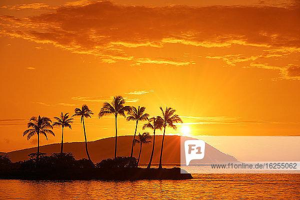 Sonnenaufgang am Kahala Beach  Wai?alae Beach Park  mit Sonnenstrahlen am glühenden Himmel  die sich im ruhigen Wasser spiegeln; Oahu  Hawaii  Vereinigte Staaten von Amerika