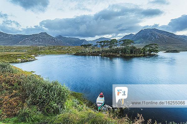 Mann mit Kanu steht am Ufer des Derryclare Lough und blickt auf Pine Island und die Berge; Connemara  County Galway  Irland