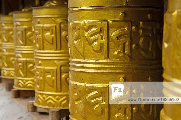 Golden coloured buddhist prayer wheels; Khunde  Khumbu Region  Nepal