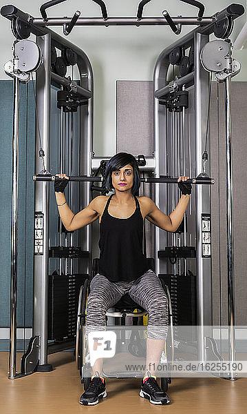 Eine querschnittsgelähmte Frau trainiert in einer Fitnesseinrichtung an einem Lat-Down-Gerät; Sherwood Park  Alberta  Kanada