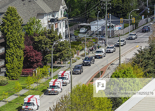 High angle view of emergency situation with a line-up of ambulances and police cars on a residential street in a neighborhood in Surrey; British Columbia  Canada