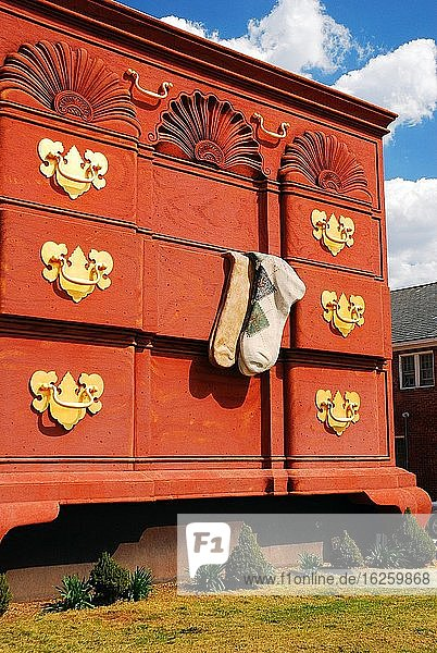 Two argyle socks hang from an open draw  the largest chest of drawers in the world  in High Point  North Carolina.