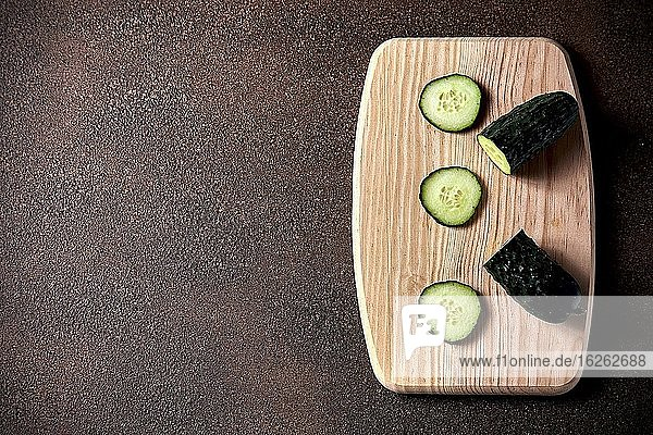 Sliced cucumber on cutting board on a rustic wooden table.