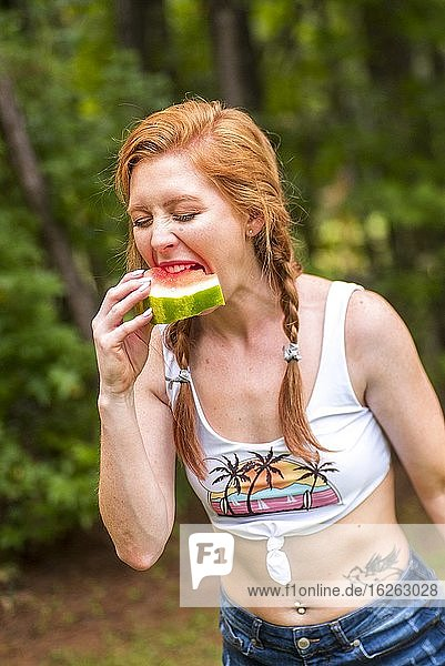A 27 year old redhead woman eating a watermelon outdoors.