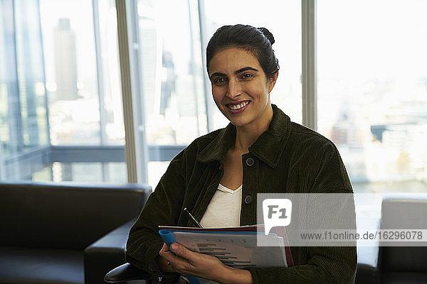 Porträt einer selbstbewussten Geschäftsfrau mit Papierkram im Büro