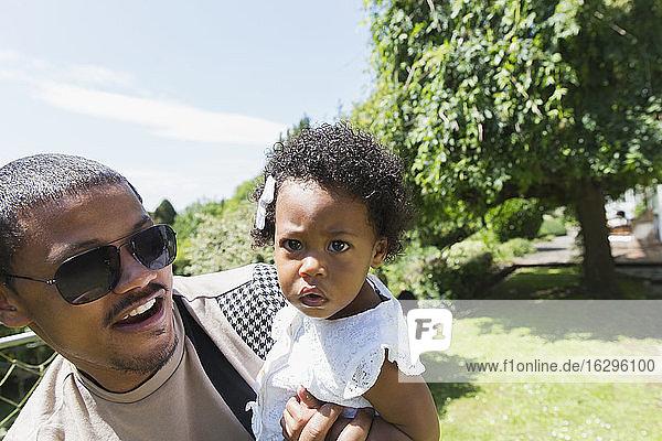 Vater hält neugierige Kleinkind-Tochter in sonnigen Sommerhinterhof